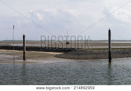 Image shows a stranded sailboat at low tide in the sand