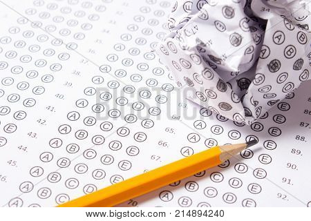 Blank multiple choice answer sheet empty with pencil and spoiled answers compressed into a ball