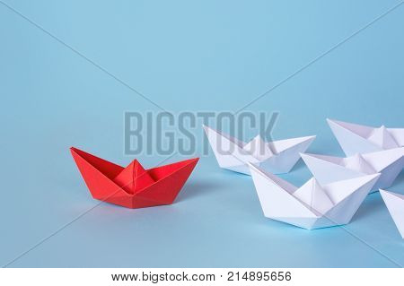 The team follows the leader. White paper boats follow the red. Copy space for text