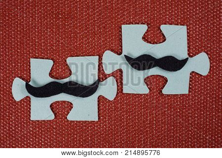 Close-up Of Two Parts Of A Puzzle. Symbolic Men With A Mustache. The Concept Of Psychological Compat