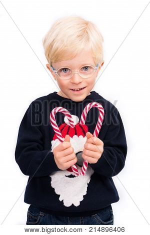 Love Christmas: A cute 4 year old boy wearing glasses and a Santa Claus pullover is holding two candy sticks, forming a heart shape on a perfect white studio background.