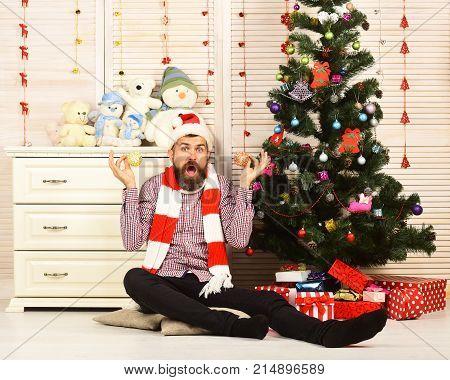 Man With Beard Holds Golden Christmas Balls Near Ears