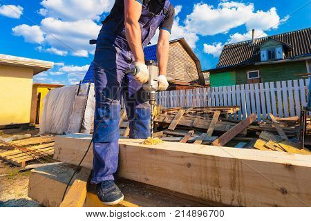 Carpenter (worker) with big professional tool (electric drill) is drilling wood beam during remodeling renovation extension restoration reconstruction and construction the house (building).