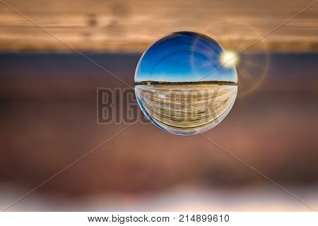 An upside down photo of a glass ball on a dock at a Virginia pier.