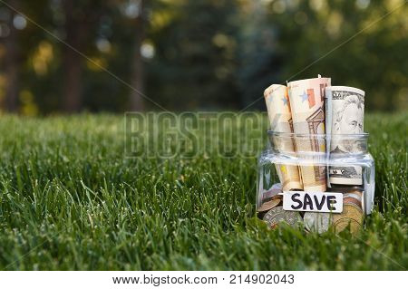 Glass jar with coins and bills on green grass background, copy space. Money box, saving money for dream, pension, vacation. Financial stability concept