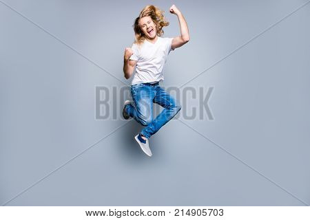 Joyful Happy Excited Young Man With Blonde Long Hair Is Screaming And Jumping Up With Raised Fists,