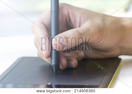 Hand of a young man writes on a graphics tablet