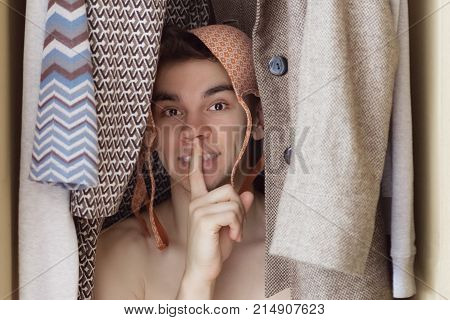 A young man with bra on his head is hiding in the closet