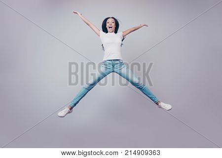 Excited mixed race brunette lady model is jumping spreading arms and legs wearing casual clothes white shoes on pure light grey background. Successful dreamy femenine girlish life relaxing mode