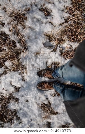 Male legs in blue jeans and winter shoes on snow, close-up. Vertical photo.