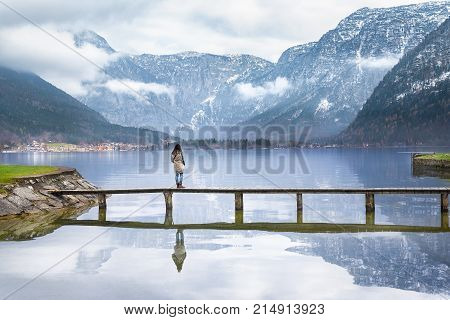 Woman on a deck over an alpine lake - Young woman standing on a wooden bridge over the Hallstatter lake enjoying the silence and the view of the Austrian Alps mountains reflected in the water.