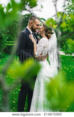 girl woman in a long white dress with a wedding bouquet along with a bearded bridegroom after a wedding ceremony on a walk in an exotic autumn park.