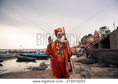 VARANASI INDIA - MARCH 14 2016: Horizontal picture of indian old saddhu holy man posing at Ganges River during day time in Varanasi India.