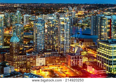 top view of the night a modern metropolis with neon lights of luminous windows and windows of houses and offices high-rise buildings parked and moving cars