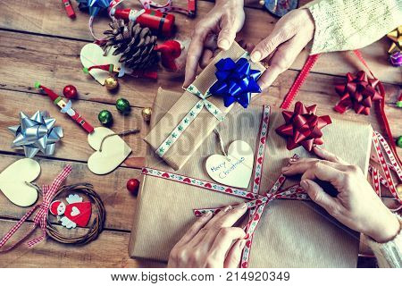 Close up of hands of two people wrapping Christmas gifts.