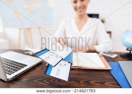 The travel agent keeps tickets for the plane in the travel agency. She offers them to clients. She smiles. On the table she has a toy plane, a laptop.