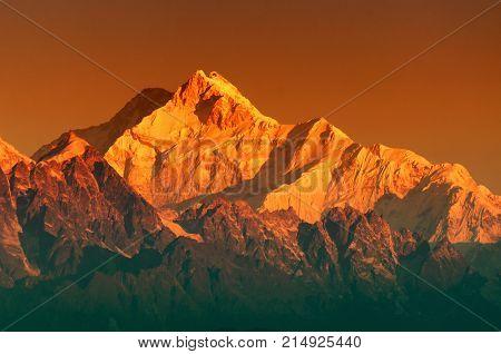 Beautiful first light from sunrise on Mount Kanchenjugha Himalayan mountain range Sikkim India. Orange tint on the mountains at dawn.