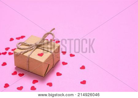 A gift wrapped in kraft paper on a pink background. Paper red hearts on a gift box
