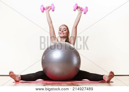 Girl Warming Up With Ball And Dumb Bell Weights.