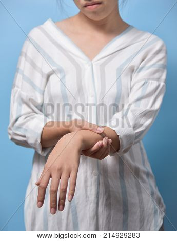 Young Asian Woman suffering from wrist pain on blue background.
