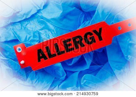 Red allergy bracelet over top blue protective gloves