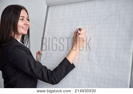 Attractive smiling young woman writing on a blank flipchart in an office as she does a presentation or promotion