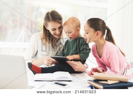 A woman works during maternity leave at home. A woman works and cares for a children at the same time. Mother of two children finds time for work at home.