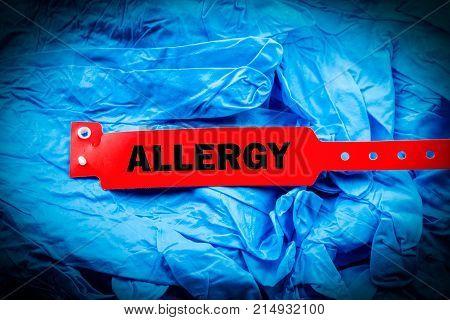 Red allergy bracelet over top of blue protective gloves