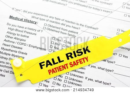 A yellow fall risk patient safety bracelet on top of a hospital questionnaire paperwork