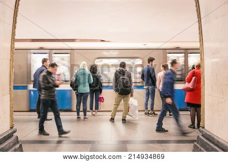 Moscow Russia - September 23, 2017: Blurry scene of arriving Metro and hurry passengers at bright platform in Moscow Metro system.
