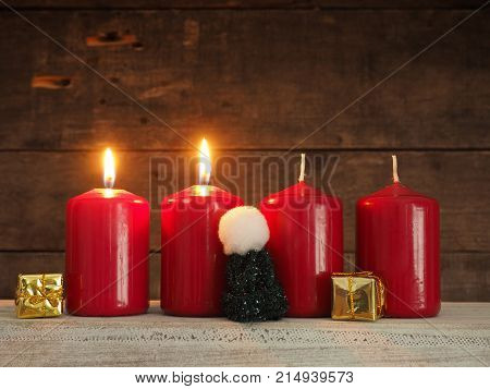 Four red Advent candles on a rustic wooden background two candles burning scond Advent Christmas concept background
