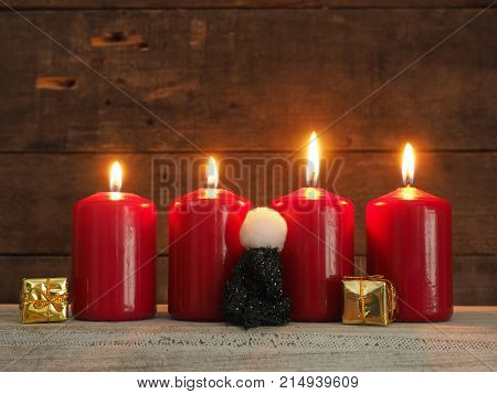 Four red Advent candles on a rustic wooden background all candles burning fourth Advent Christmas concept background
