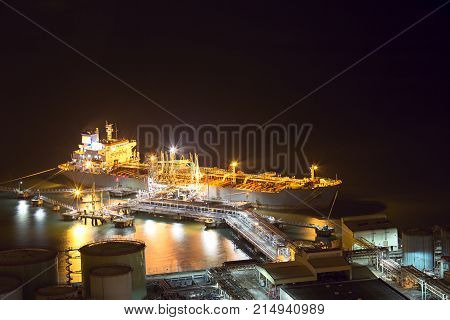 Night scene aerial view of big oil tanker ship loading at oil depot pier in power industry with copy space