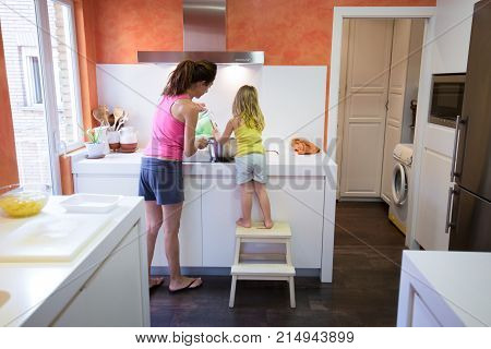 Back Of Woman And Child Cooking Together In The Kitchen