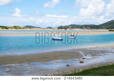 Ngunguru Harbour at low tide with boats moored in the river estuary near the sandspit - in Northland North Island New Zealand NZ