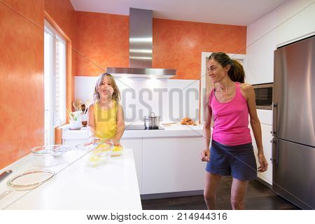 Child In Kitchen Looking And Stiking Out Tongue Next To Mother