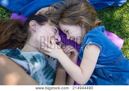 woman mother and four years old blonde child laughing together looking with complicity lying on towels in the green grass of park