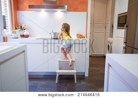 Four years old blonde child climbing on stool o ladder to cook in electrical cooktop with a saucepan alone in the kitchen