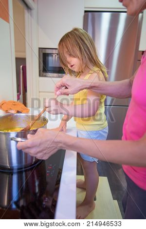 Little Child Helping To Cook Her Mother In Kitchen