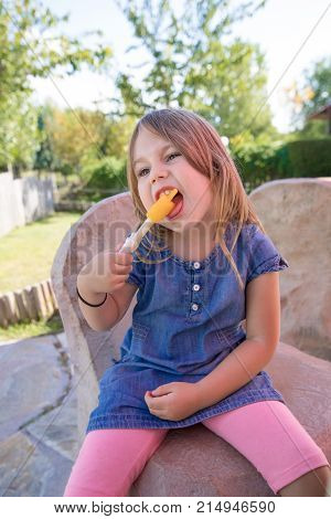 four years old blonde girl with blue denim dress sitting in public park biting orange or yellow ice lolly or popsicle