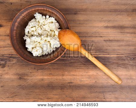 Clay bowl with cottage cheese on old wooden table. Dairy product cottage cheese in brown ceramic bowl with wood spoon, top view. Template for menu, poster or print design.