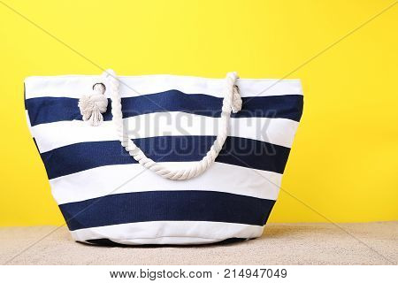 Striped summer bag on the beach sand