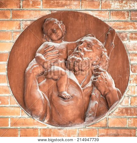 Icon of Jesus and St. Joseph made of terracotta applied on the exterior wall of a church.