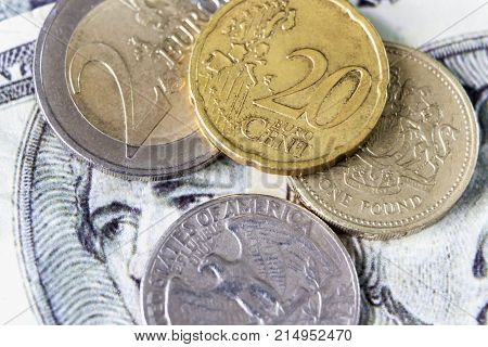 British one pound coin and quarter dollar coin placed on dollar banknote background.