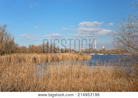 Tall chimney in the swampland under blue sky