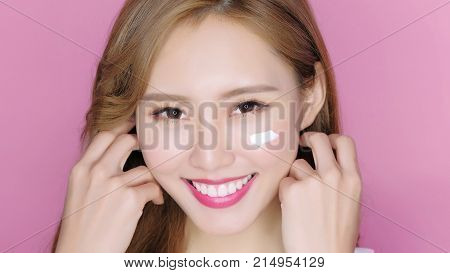 beauty makeup woman smile and applying moisturizer cream on her pretty face