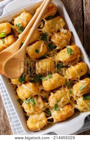 Casserole Of Tater Tots With Cheese And Herbs Close Up In A Baking Dish. Vertical Top View