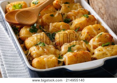 Hot Baked Tater Tots With Cheese, Meat, Corn And Parsley Close-up In On The Table. Horizontal