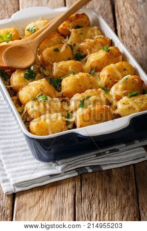 Homemade Baked Tater Tots With Cheese, Meat And Greens Close Up In A Baking Dish. Vertical
