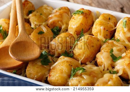 Baked Tater Tots With Cheese And Herbs Close Up In A Dish Baking Dish. Horizontal